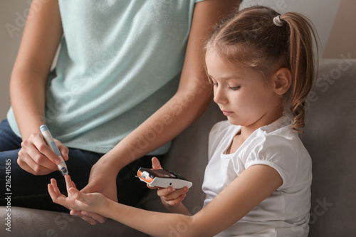 Cuadros en Lienzo  Woman and her diabetic daughter with lancet pen and digital glucometer taking bl