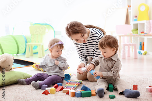 Photo  Young nanny playing with little children, indoors