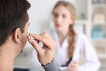 Man Putting On Hearing Aid In Doctor's Office