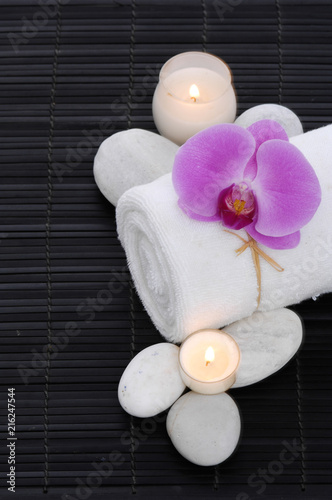 Spa setting with orchid on towel ,stones .candle on mat