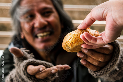 Fotografie, Tablou Hand giving bread or food to blurred happy face homeless male