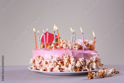 Plate with tasty birthday cake and burning candles on table Wallpaper Mural