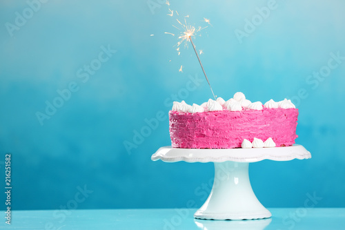 Stand With Delicious Birthday Cake And Sparkler On Table Against Color Background
