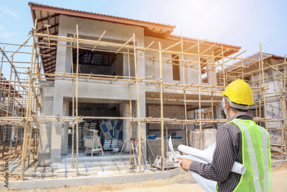 Fototapeta Professional engineer architect worker with protective helmet and blueprints paper at house building construction site