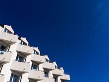White Hotel Balconies Against Blue Sky