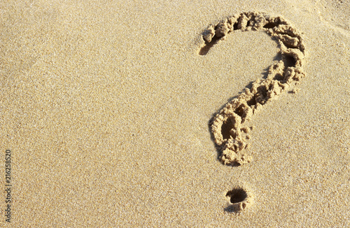 Vászonkép question mark drawn on a sandy beach, close-up, top view