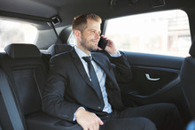 Executive Businessman At The Back Of Car Using A Mobile Phone