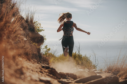 Valokuva Female running over rocky trails on the hillside.