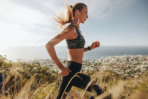 Woman training for marathon on mountain trail.
