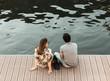 Couple assis au bord d'un quai en ville