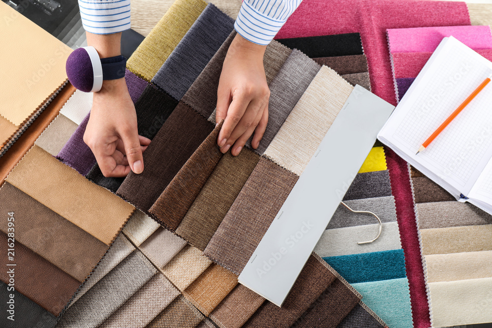 Fototapety, obrazy: Young woman choosing among upholstery fabric samples, closeup. Interior design