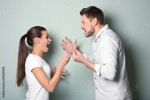 Young couple arguing on color background Canvas Print