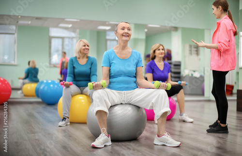 Group of mature women with young coach training in modern gym