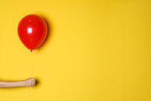 Woman Holding Red Balloon On Color Background