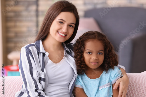 Young woman with little African-American girl indoors Wallpaper Mural