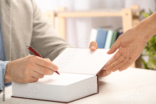 Writer signing autograph in book at table, closeup Canvas Print