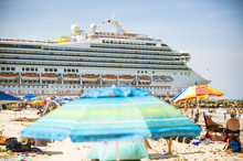 Cruise Ship Leaves Port And Passes People With Umbrellas On South Beach.