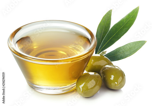Bowl of olive oil and green olives with leaves
