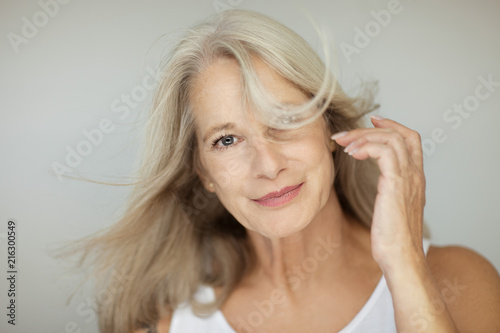 Obraz stunning beautiful and self confident best aged woman with grey hair smiling into camera, portrait with white background  - fototapety do salonu
