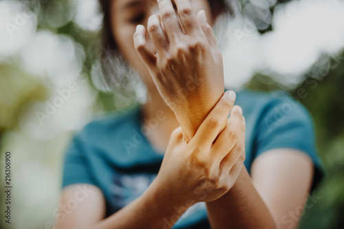Photo Close up young woman Left wrist pain , office syndrome , health care concept