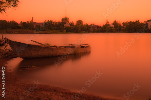 Foto auf Leinwand Violett rot The boat near the shore of the river or the lake in the rays of setting or rising sun. The summer countryside landscape in the warm orange colours