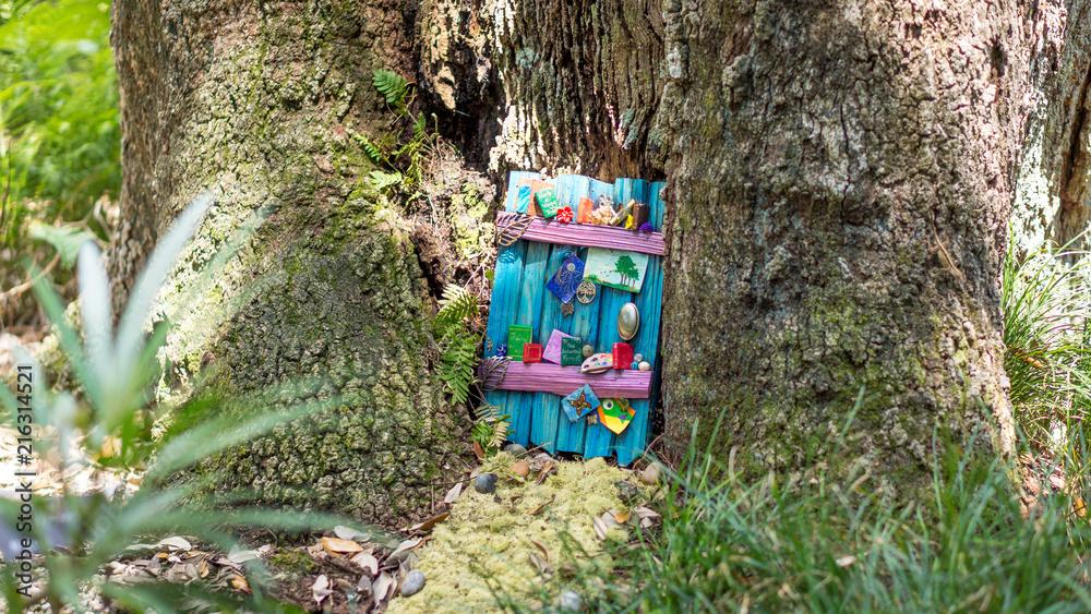 Fototapeta Decorated fairy door in a tree