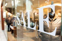 Closeup Of Sale Sign On Clothes, Clothing, Apparel Retail Store, Shop Window In Shopping Mall
