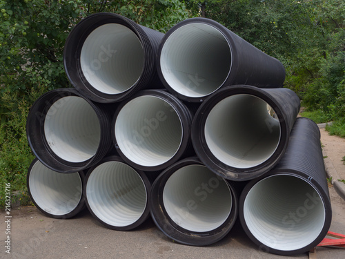 Sewer pipes are stacked in front of the house. Canvas-taulu