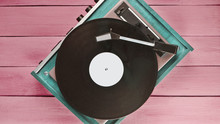 Vintage Vinyl Player On Red Wooden Background. Top View. Retro Media Technologies.