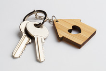 House Keys With House Shaped Keychain On White Background
