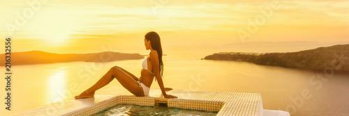 Fototapeta Luxury travel Santorini hotel woman by resort swimming pool at sunset - Bikini body model sunbathing banner panorama. obraz