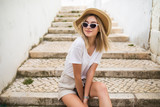 Fototapeta Na drzwi - Beautiful young caucasian woman smiling in urban background. Blond girl wearing casual clothes in the street.