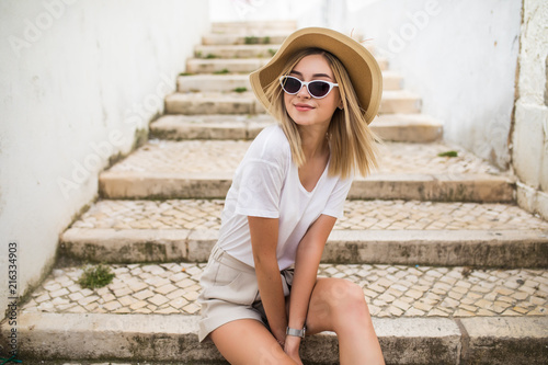 Beautiful young caucasian woman smiling in urban background. Blond girl wearing casual clothes in the street.