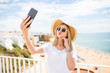 Pleasant girl in sunglasses and hat touching her cheek while making selfie on sea background.