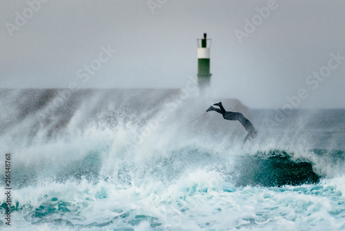 Valokuva  Surfer jumping over a wave during a windy day