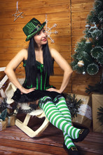 Brunette Girl In An Elf Costume In A Green Corset And Short Skirt In Green And White Striped Golf In A Green Cylinder With A Pot Of Gold, The Concept Of St. Patrick's Day For The New Year