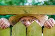 ein neugieriger Nachbar sieht über den Gartenzaun