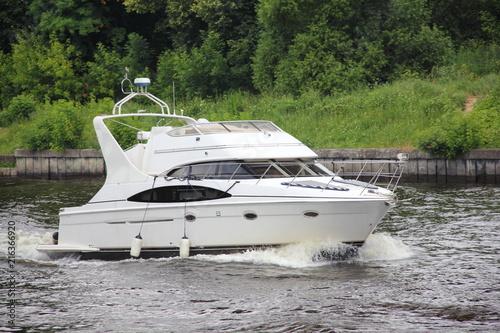 Slika na platnu Travel, luxury water recreation on boat - a white motor yacht slowly floating al