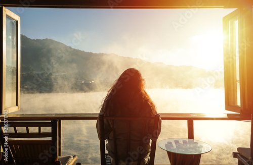 Valokuva  A woman sitting alone in a room among fog and looks outside opened window seeing mountain and sunrise in a cold winter day