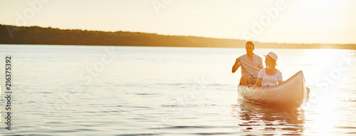 Fotografie, Obraz Smiling young couple canoeing on a lake in the summer