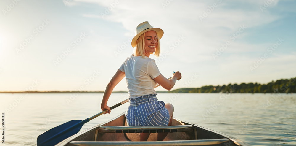 Fototapety, obrazy: Smiling woman canoeing on a still lake in the summer