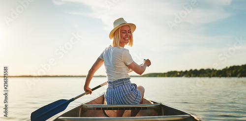 Fényképezés  Smiling woman canoeing on a still lake in the summer