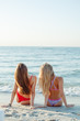 Two sexy women in swimsuit siting on sand. Having fun in the sea at Sunrise