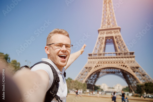 Foto  Man tourist with backpack and wearing glasses makes selfie photo on background of Eiffel Tower in Paris, France