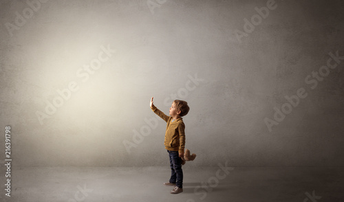 Little waggish kid staying alone in a big empty room with his plush Fototapet
