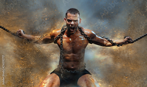 Fotografia Muscular man slave in chains in a sand storm, the prisoner