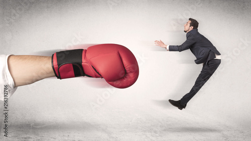 Papiers peints Echelle de hauteur Businessman gets fired from his job by a huge hand in boxing gloves