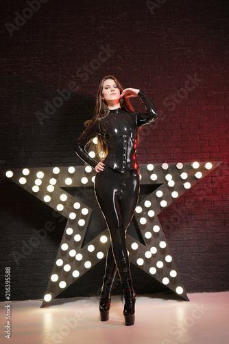 hot fetish girl posing in latex rubber catsuit and tight corset near the shining Poster Mural XXL