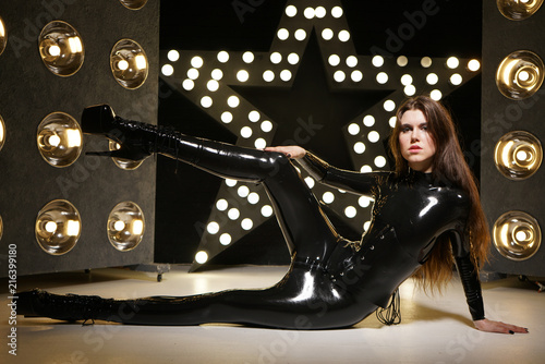 Valokuva hot kinky woman wearing latex rubber catsuit and fetish corset posing in the bla