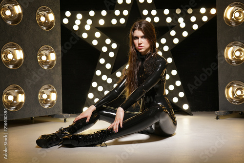 Photo hot kinky woman wearing latex rubber catsuit and fetish corset posing in the bla
